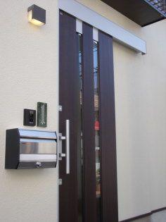 引き戸の玄関ドアと表札とポスト